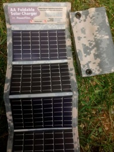 A PowerFilm Solar AA charger unfolded and charging on left, folded panel on right.