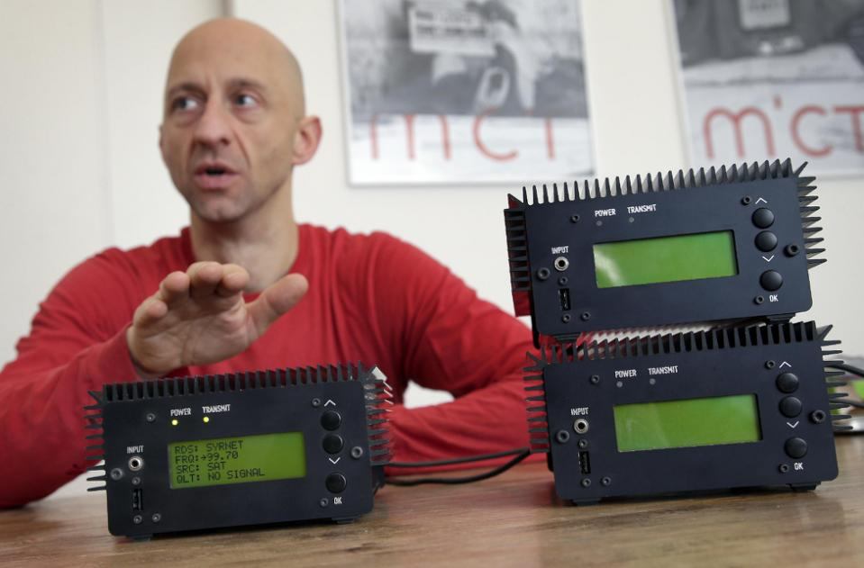 In this photo taken Monday, Dec. 21, 2015, Philipp Hochleichter of the MICT (Media in Cooperation and Transmission) organization talks behind Pocket FM Radio Transmitters in Berlin, Germany. As part of the Syrian radio networking project, MICT has designed small modular FM transmitters. (AP Photo/Michael Sohn)